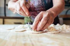 Manos arrugadas de las abuelas que ponen el relleno en pasta imágenes de archivo libres de regalías