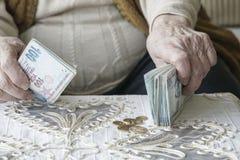 Manos arrugadas que cuentan billetes de banco de la lira turca Imagen de archivo