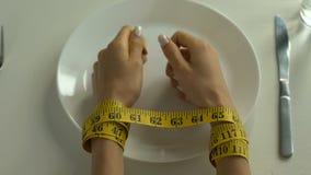 Manos atadas con la cinta métrica que miente en la placa, obsesión con la dieta, calorías almacen de video