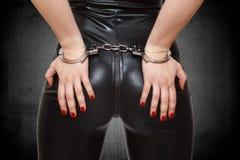 Manos atractivas del dominatrix en asno en esposas Imagen de archivo