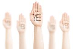 Manos aumentadas al cielo y a decir sí. Fotografía de archivo libre de regalías