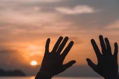 Manos aumentadas contra el cielo de la puesta del sol Imagen de archivo libre de regalías