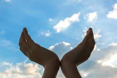 Manos aumentadas en fondo del cielo azul fotografía de archivo