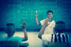 Manos aumentadas en sala de clase en la escuela de país entre el compañero de clase Fotografía de archivo libre de regalías
