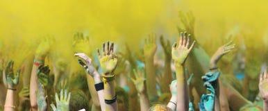 Manos aumentadas para arriba en el festival de Holi Foto de archivo libre de regalías