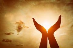 Manos aumentadas que cogen el sol en el cielo de la puesta del sol Concepto de espiritualidad, bienestar, energía positiva Foto de archivo libre de regalías
