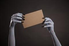 Manos blancas de la bruja con los clavos negros que sostienen la cartulina en blanco Imagenes de archivo