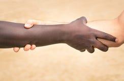 Manos blancos y negros en apretón de manos moderno contra racismo Fotografía de archivo libre de regalías
