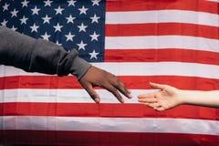 Manos blancos y negros en fondo de la bandera americana imagen de archivo