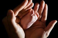 Manos que llevan a cabo el pie del bebé Fotografía de archivo libre de regalías