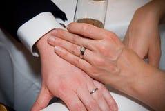 Manos casadas de los pares con el vidrio de Champán Foto de archivo
