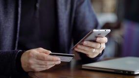 Manos caucásicas jovenes que compran mercancías de Internet en su smartphone con su tarjeta de crédito almacen de video
