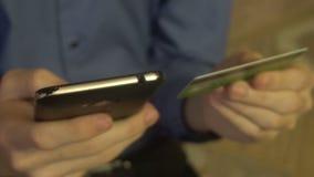 Manos caucásicas jovenes que compran mercancías de Internet en su smartphone con su tarjeta de crédito metrajes