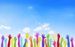 Manos coloridas aumentadas con el cielo azul Foto de archivo libre de regalías