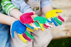 Manos coloridas de los niños que juegan afuera Fotografía de archivo libre de regalías