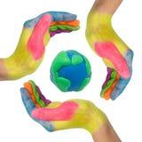 Manos coloridas que hacen un círculo alrededor del globo de la tierra imagen de archivo