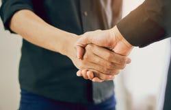 Manos comunes de dos hombres de negocios después de negociar un acuerdo acertado del negocio, y el apretón de manos junto foto de archivo