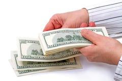 Manos con 100 billetes de dólar Imagen de archivo