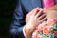 Manos con el anillo de bodas en hombro de las novias Fotos de archivo