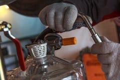 Manos con el coche de la reparación de los guantes imagenes de archivo