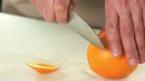 Manos con el cuchillo que pela la naranja almacen de metraje de vídeo