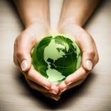Manos con el globo de la tierra verde Fotos de archivo