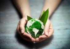 Manos con el globo verde del mundo del eco - los E.E.U.U. Imágenes de archivo libres de regalías