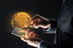 Manos con el holograma del smartphone y de la tierra Fotos de archivo