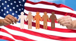 Manos con el pictograma de la gente sobre bandera americana Imagen de archivo