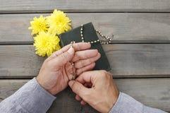 Manos con el rosario sobre la Sagrada Biblia vieja Fotos de archivo libres de regalías