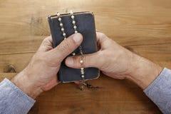 Manos con el rosario sobre la Sagrada Biblia vieja Imágenes de archivo libres de regalías