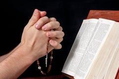 Manos con el rosario y la biblia Fotos de archivo