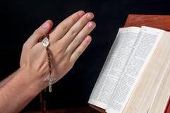 Manos con el rosario y la biblia Imagen de archivo libre de regalías