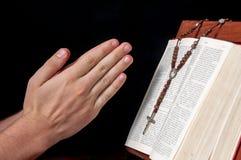 Manos con el rosario y la biblia Imágenes de archivo libres de regalías