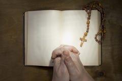 Manos con el rosario y un libro viejo Fotografía de archivo libre de regalías