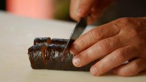 Manos con el sushi del corte del cuchillo almacen de video