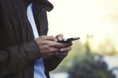 Manos con el teléfono móvil Fotografía de archivo libre de regalías