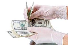 Manos con guantes con 100 billetes de dólar Foto de archivo libre de regalías