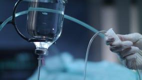 Manos con guantes que controlan el contador del descenso Botella de la infusión Tratamiento de quimioterapia almacen de video