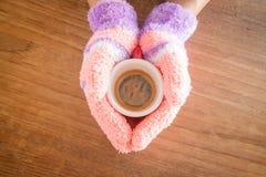 Manos con guantes que sostienen la taza de café Imágenes de archivo libres de regalías
