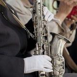 Manos con guantes y un saxofón Fotos de archivo libres de regalías