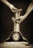 Manos con la arena y el reloj Foto de archivo libre de regalías