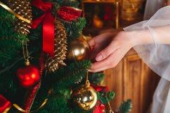 Manos con la bola Mujer joven que adorna el árbol de navidad con las bolas rojas en casa Fotos de archivo