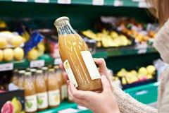 Manos con la botella de zumo de manzana fresco en tienda Imágenes de archivo libres de regalías