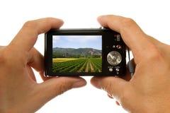 Manos con la cámara digital de la foto que toma el cuadro Fotografía de archivo libre de regalías
