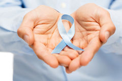 Manos con la cinta azul de la conciencia del cáncer de próstata Fotografía de archivo libre de regalías