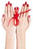 Manos con la cinta roja. Fotos de archivo libres de regalías