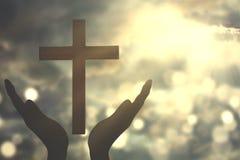 Manos con la cruz que adora a DIOS Fotos de archivo