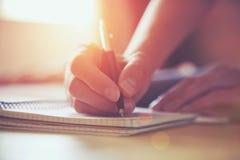 Manos con la escritura de la pluma en el cuaderno Foto de archivo libre de regalías