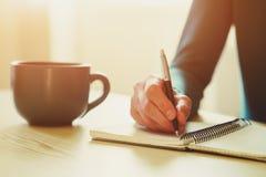 Manos con la escritura de la pluma en el cuaderno fotografía de archivo libre de regalías